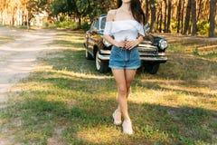 Señora hermosa que se coloca cerca del coche retro una muchacha en una blusa blanca y pantalones cortos de los vaqueros está sost fotografía de archivo libre de regalías