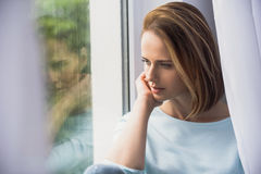 Señora hermosa que se sienta delante de ventana Fotos de archivo libres de regalías