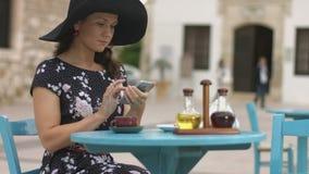 Señora hermosa que se sienta en el café de la calle, charlando en línea, mandando un SMS en smartphone metrajes