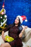 Señora hermosa que sonríe al lado del árbol de navidad encendido Fotos de archivo