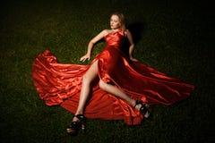 Señora hermosa In Red Dress Lying en hierba Fotos de archivo