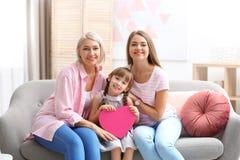 Señora, hija y nieto maduros hermosos con el regalo en casa Día feliz del ` s de las mujeres fotografía de archivo