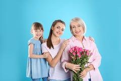 Señora, hija y nieto maduros hermosos con las flores Día feliz del ` s de las mujeres foto de archivo libre de regalías