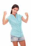 Señora hispánica bonita en camisa azul con los brazos para arriba Fotografía de archivo