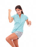 Señora hispánica joven en camisa azul con el brazo para arriba Imagenes de archivo