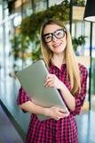 Señora independiente del negocio hermoso en ropa de sport elegante con el ordenador portátil en las manos, mirando la cámara y so fotografía de archivo libre de regalías