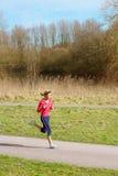 Señora Jogging en un parque fotografía de archivo