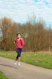 Señora Jogging en un parque fotos de archivo