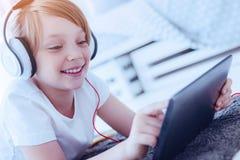 Señora joven adorable que disfruta de la música que juega en sus auriculares Foto de archivo