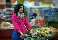 Señora joven agradable en el supermercado Imagenes de archivo