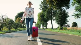 Señora joven alegre con la maleta que camina en el camino almacen de metraje de vídeo