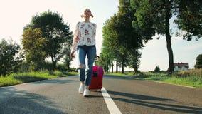 Señora joven alegre con la maleta que camina en el camino metrajes
