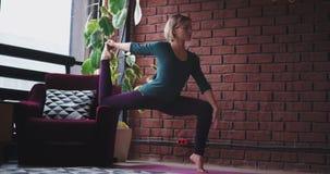 Señora joven apuesta en una ropa de deportes en casa usando un sofá para hacer un ejercicio duro usando la yoga Tehnic a estirar almacen de metraje de vídeo
