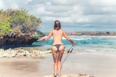 Señora joven atractiva en el bikini que salta en la playa con la fruta sana cruda fresca de la piña Concepto feliz de las vacacio Imágenes de archivo libres de regalías