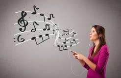 Señora joven atractiva que canta y que escucha la música con musica Foto de archivo libre de regalías