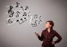 Señora joven atractiva que canta y que escucha la música con musica Fotos de archivo libres de regalías