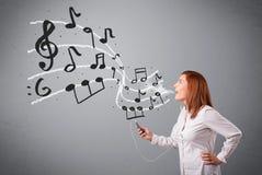 Señora joven atractiva que canta y que escucha la música con musica Foto de archivo