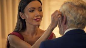 Señora joven atractiva que liga con el viejo hombre de negocios, frotando ligeramente la cara, servicio de acompañamiento fotos de archivo