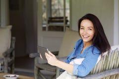 Señora joven atractiva que se relaja con la tableta de la pantalla táctil Fotos de archivo libres de regalías