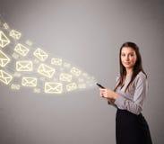 Señora joven atractiva que sostiene un teléfono con los iconos del mensaje Imagen de archivo libre de regalías