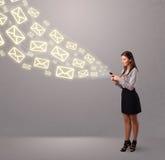 Señora joven atractiva que sostiene un teléfono con los iconos del mensaje Fotos de archivo