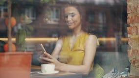 Señora joven atractiva usando smartphone en el café que se relaja con el artilugio y el café almacen de video