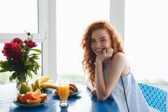 Señora joven bastante alegre del pelirrojo cerca de las flores y de las frutas imagenes de archivo