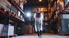 Señora joven bonita que camina entre los estantes en trastero enorme y que hace notas durante la inspección en fábrica metrajes