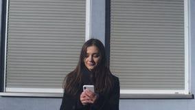 Señora joven bonita que se coloca al aire libre que mecanografía en el smartphone, concertando la cita almacen de metraje de vídeo