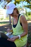 Señora joven con el ordenador portátil en el parque Foto de archivo