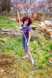 Señora joven con el rastrillo spring cleaning el jardín Imagen de archivo libre de regalías
