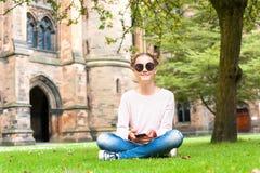 Señora joven con el teléfono móvil que se sienta en Glasgow University Garde Imágenes de archivo libres de regalías