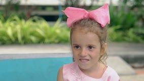 Señora joven con sonrisas púrpuras enormes del arco contra piscina almacen de video