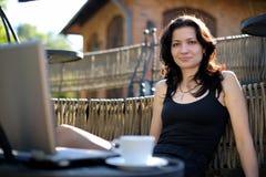 Señora joven con un cuaderno en un café del verano Imagen de archivo