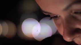Señora joven concentrada con maquillaje natural en el bokeh brillante metrajes