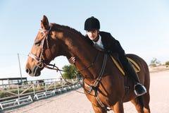 Señora joven concentrada que se sienta en su caballo Foto de archivo libre de regalías
