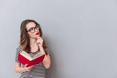 Señora joven de pensamiento que se coloca sobre el libro de lectura gris de la pared Fotos de archivo
