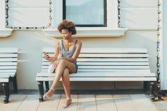 Señora joven del Afro con el teléfono móvil en banco de la calle Foto de archivo
