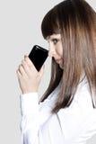 Señora joven del asunto con el teléfono Foto de archivo libre de regalías