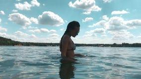 Señora joven del encanto en el traje de baño de las rayas que presenta en el mar almacen de video