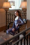 Señora joven dulce blanda que se sienta en un viejo interior en un vestido del vintage en una silla retra que mira pensativamente imagenes de archivo