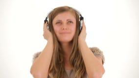 Señora joven In Earphones Listening a la música y almacen de video