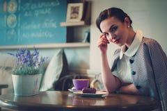 Señora joven elegante solamente en un café fotos de archivo