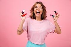 Señora joven emocional feliz que lleva a cabo esmalte de uñas y que mira la cámara Imagenes de archivo