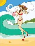 Señora joven en bikini rojo que camina a lo largo de la playa Foto de archivo libre de regalías
