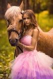 Señora joven en el bosque con su caballo Foto de archivo