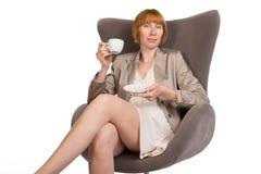 Señora joven en el estilo de la oficina que se sienta en silla moderna con una taza de café Fotografía de archivo