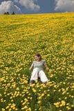 Señora joven en el prado por completo de flores Imagenes de archivo