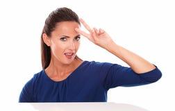 Señora joven en la blusa azul que hace una muestra de la victoria Imagen de archivo libre de regalías