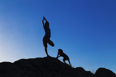 Señora joven en la posición de la yoga con el perro respecto a las rocas Foto de archivo